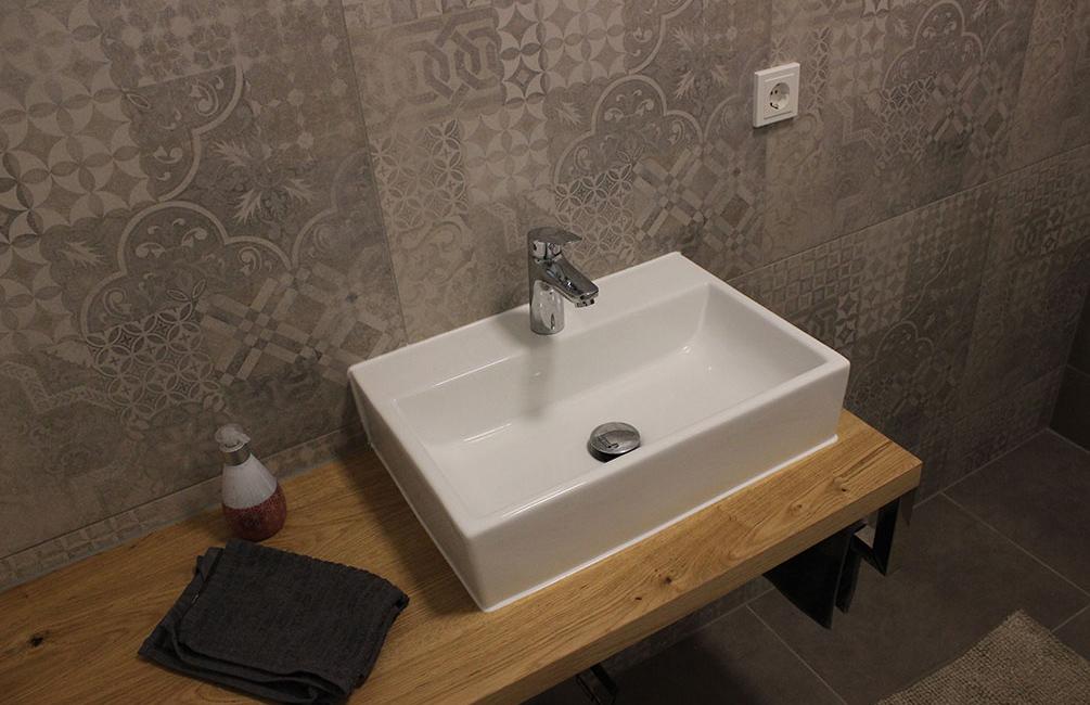 Durch wiederkehrende Holz-Elemente und die Fliesen-Motiv hat die Toilette eine einzigartige Atmosphäre.