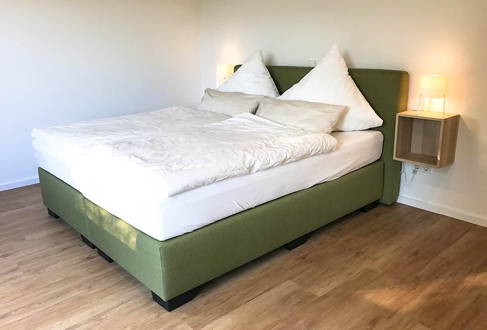 Das gemütliche grüne Boxspringbett lädt dazu ein, das Bett nicht zu verlassen!