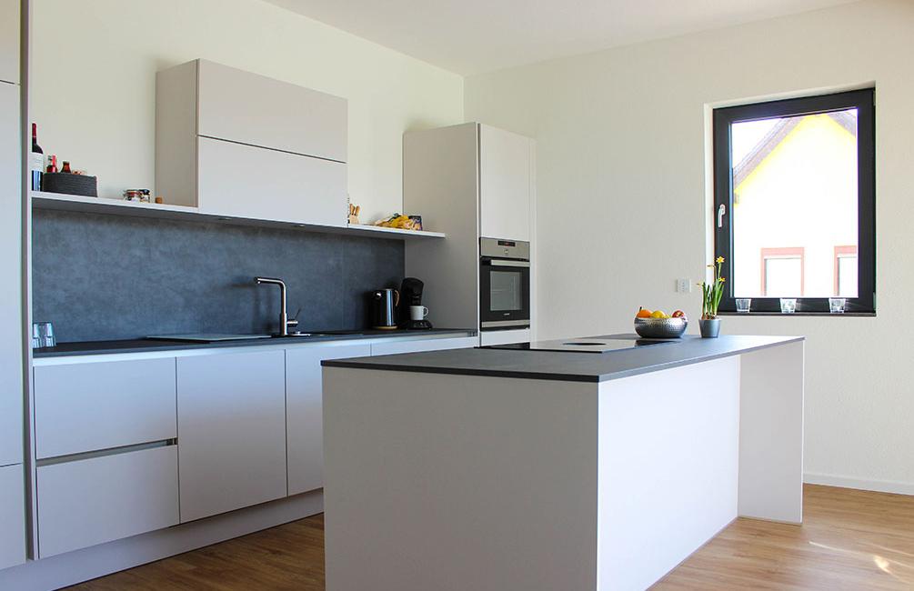 Durch große Fenster ist auch die große Küche im offenen und hellen Wohnbereich optimal ausgeleuchtet.