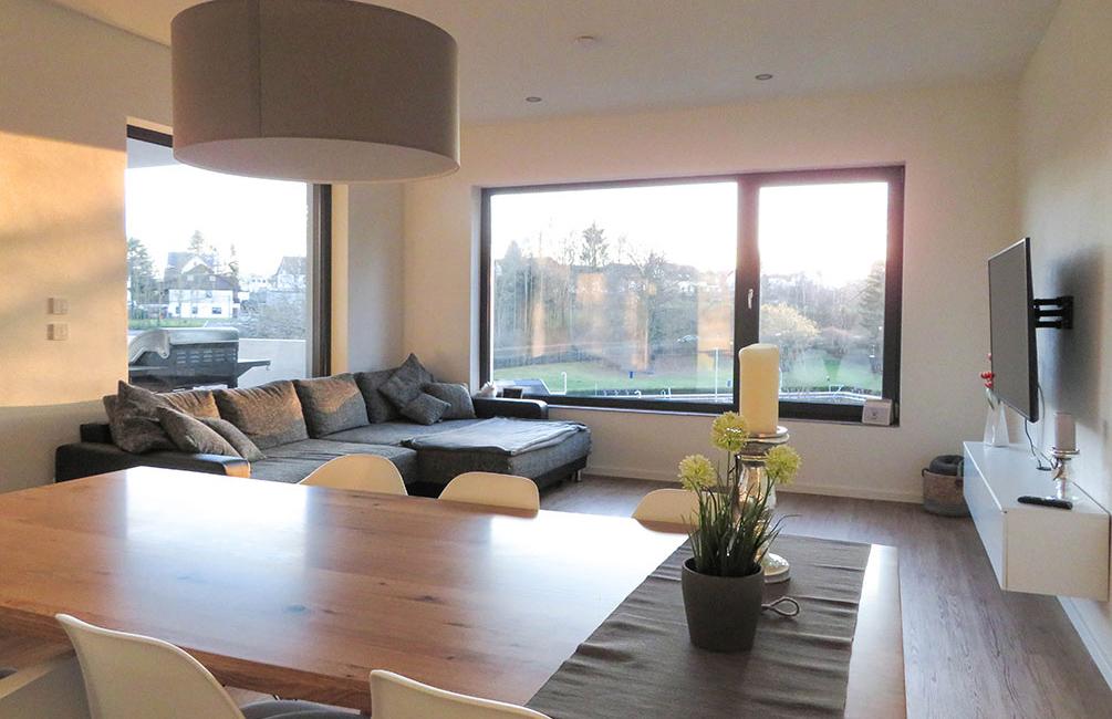 Ein großer Esstisch aus hellbraunem Holz mit einem glatten Finish passt sich dem offenen und hellen Wohnbereich mit großer Küche perfekt an.